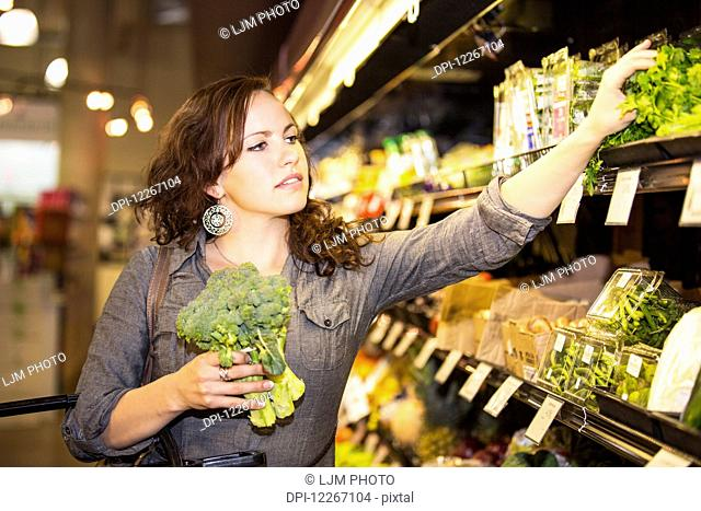 Young woman shopping in organic market for groceries; St. Albert, Alberta, Canada