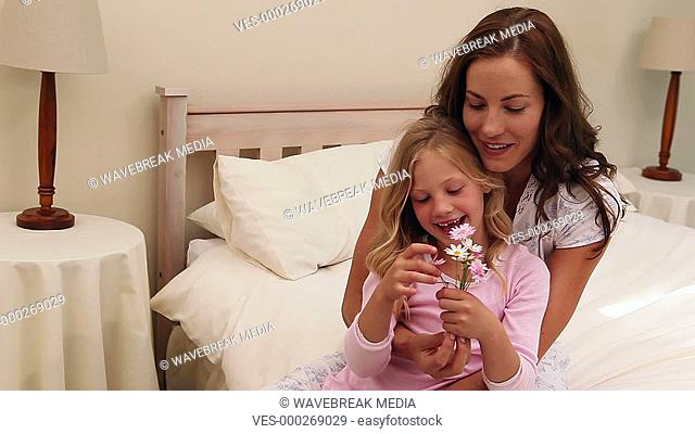 Mother sitting with her little girl holding flowers