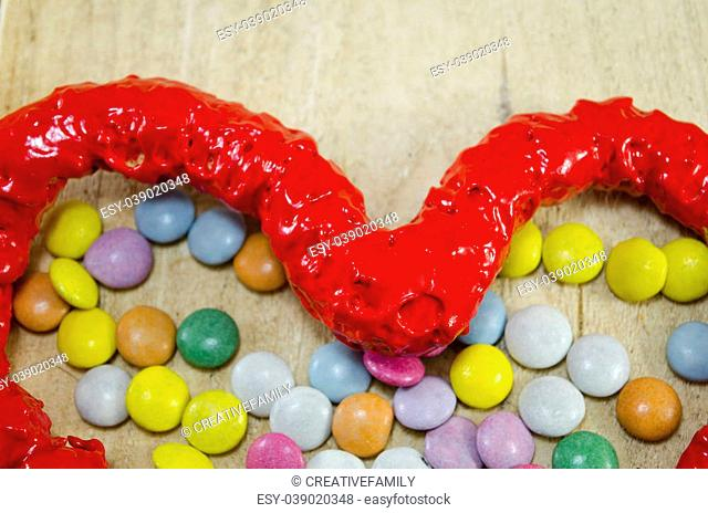 Red candy heart and colorful candy bombons on a wooden table, closeup