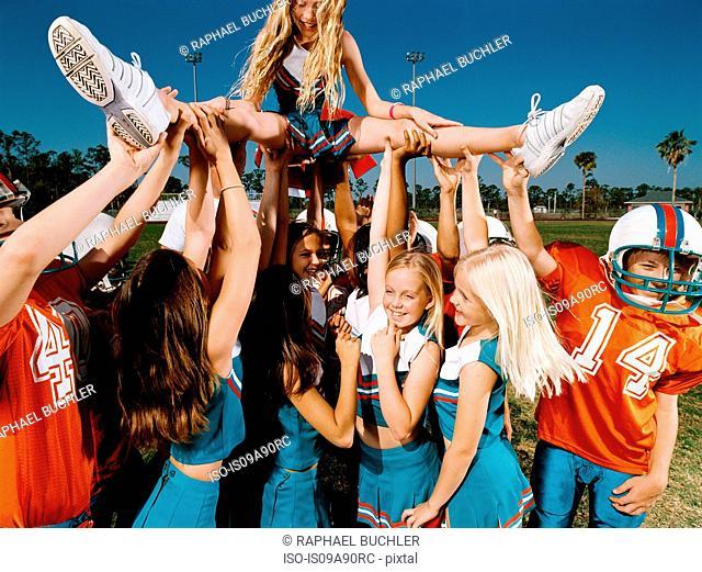 Cheerleaders and American football players lifting young woman
