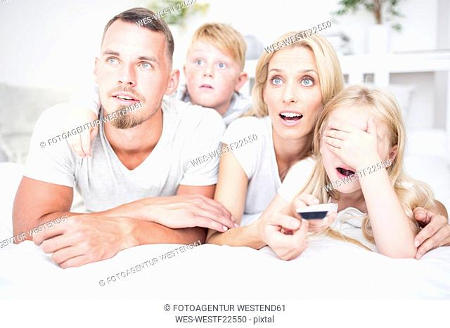 Happy family lying in bed watching Tv
