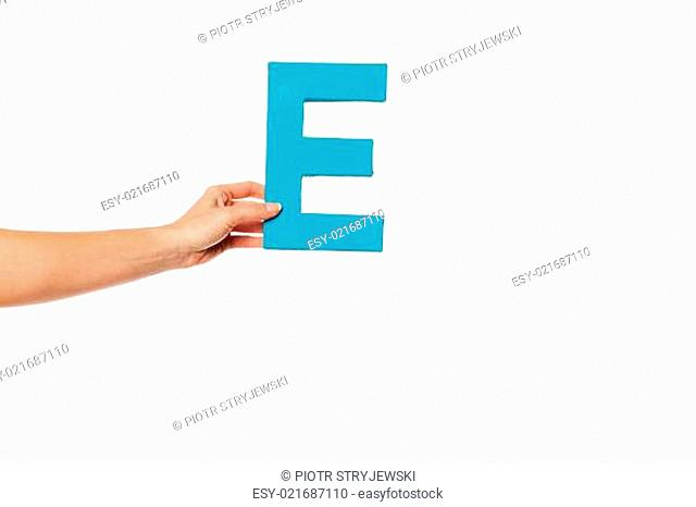 hand holding up the letter E from the left