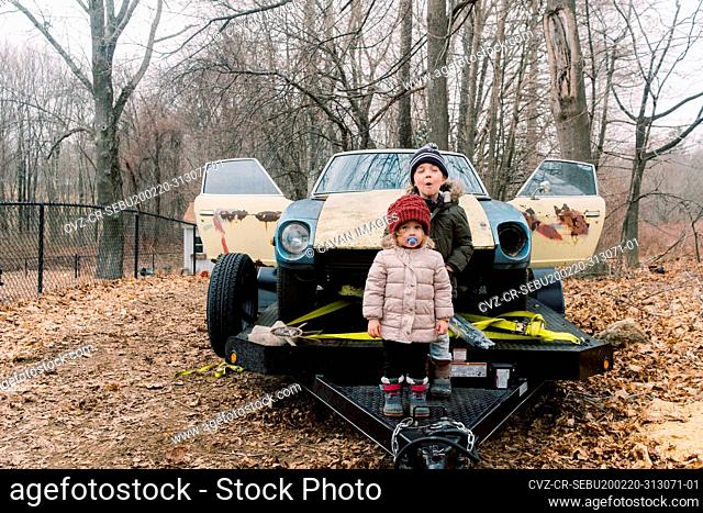 Two siblings posing next to an old rusty parts car on a trailer