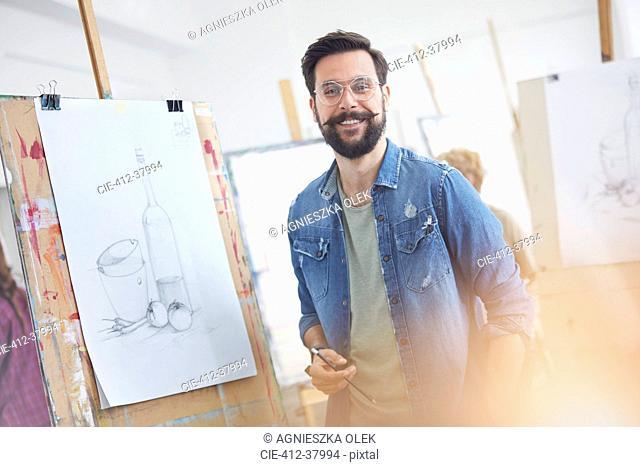 Portrait smiling male artist with beard sketching in art class studio