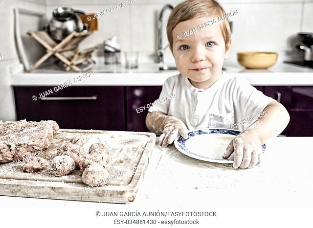Baby boy preparing meatballs. He is looking straight to the camera