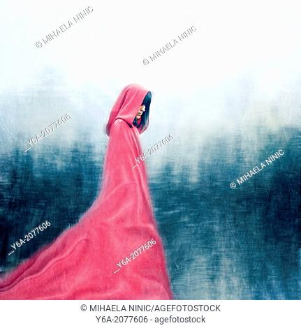 Woman wearing red cloak walking outdoors