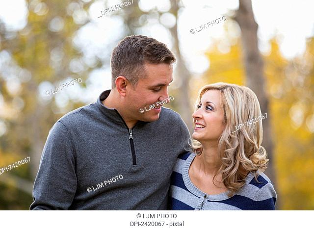Married couple spending quality time together in a park in autumn; Edmonton, Alberta, Canada