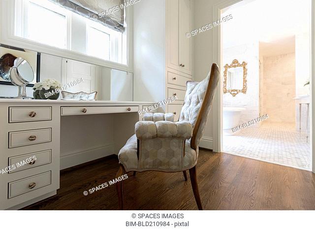 Armchair at vanity in ornate bedroom