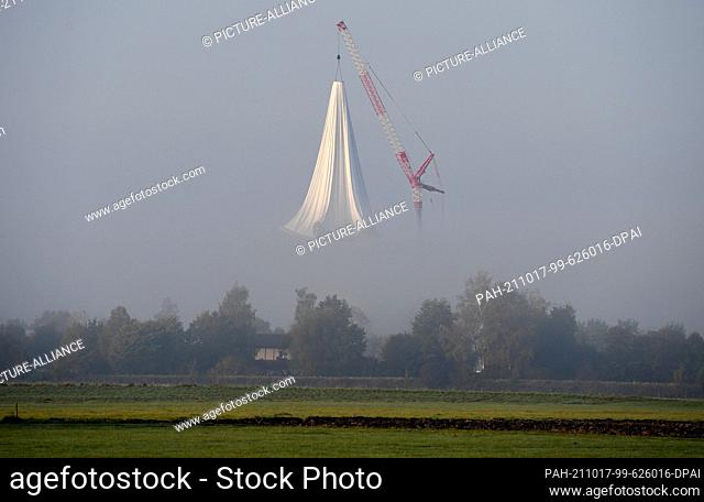 17 October 2021, Bavaria, Raisting: A new supporting air envelope is lowered on a crane above the industrial monument Radom