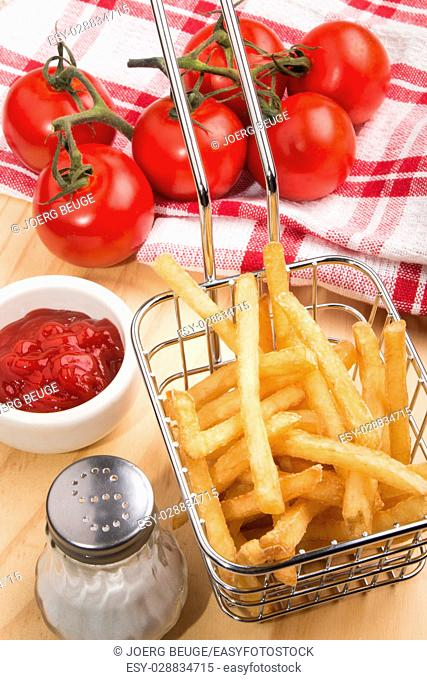 golden brown french fries in a basket with tomato, ketchup and salt