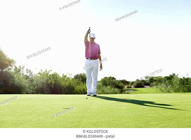 Hispanic golfer aiming on golf course