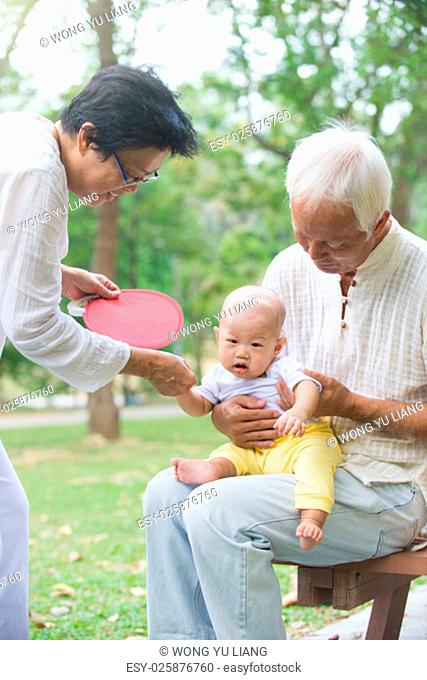 chinese grandfather and grandmother playing with baby grandson at outdoor.