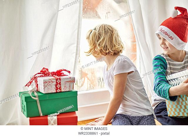 Christmas morning in a family home. A girl on a window seat looking out