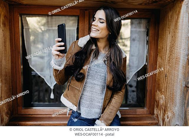 Happy young woman at the window of a wooden house taking a selfie