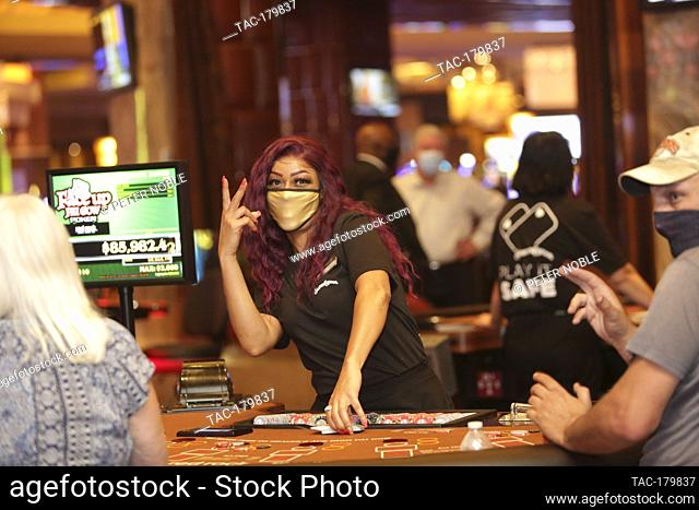 Las Vegas, NV - June 4, 2020: A dealer flashes a sign during the Grand Re-Opening of Red Rock Casino Resort & Spa at 12:01 AM on June 4, 2020 in Las Vegas
