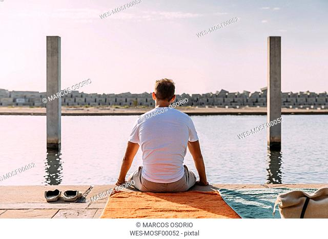 Young man sitting on a pier at the sea