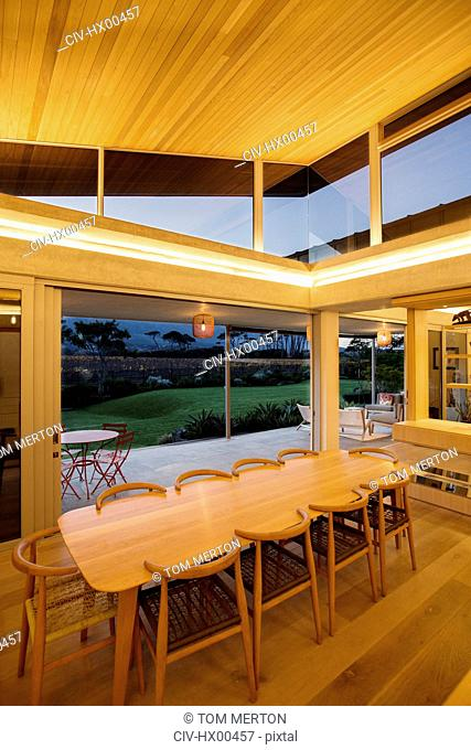 Illuminated slanted wood ceiling over long dining table