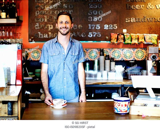 Portrait of young man working behind counter in cafe