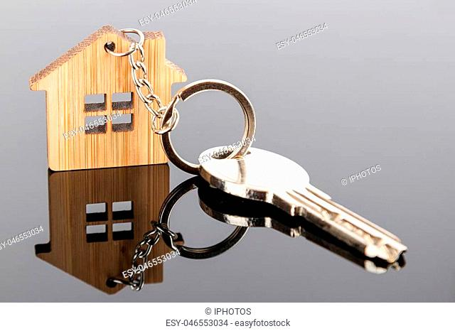 A key on house shaped wooden keychain