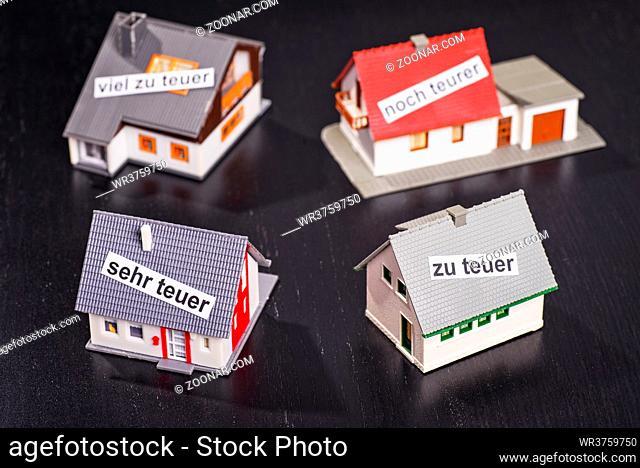 Häuser mit Beschriftungen, die zu hohe Preise symbolisieren