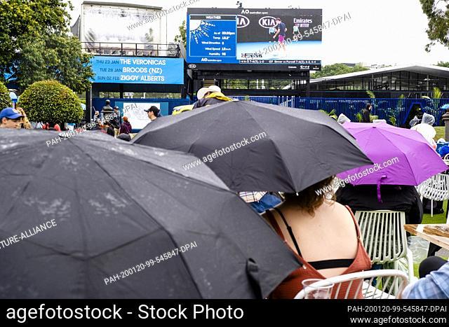 20 January 2020, Australia, Melbourne: Tennis: Grand Slam, Australian Open. Spectators sit under umbrellas in front of a video screen