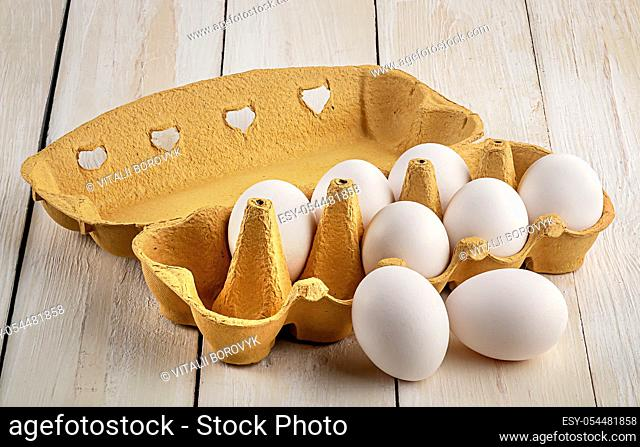 White eggs near paper tray on white table