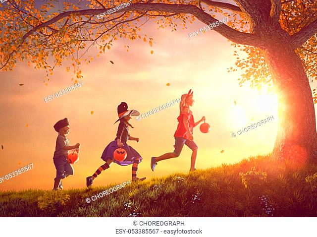 Happy brother and two sisters at Halloween. Funny kids in carnival costumes outdoors. Cheerful children and pumpkins on sunset background