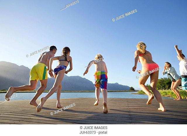 Multi generation family running to jump into lake from a jetty