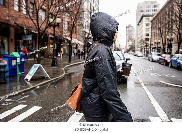 Young woman on rainy pedestrian crossing, Seattle, Washington State, USA