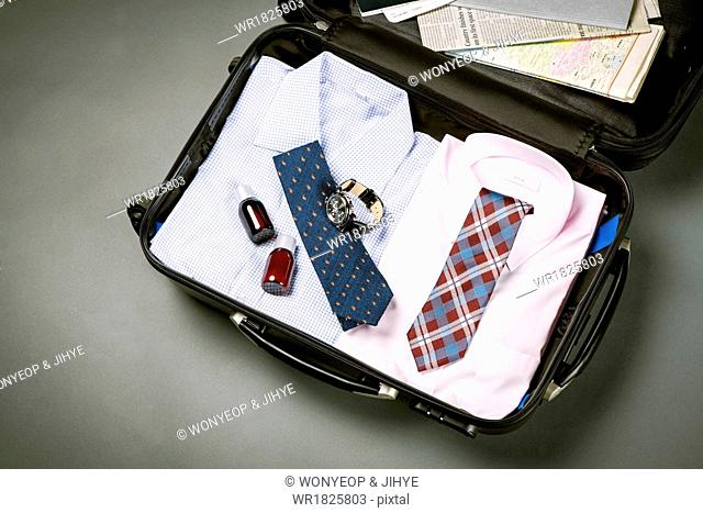 a business mans accessories in a luggage