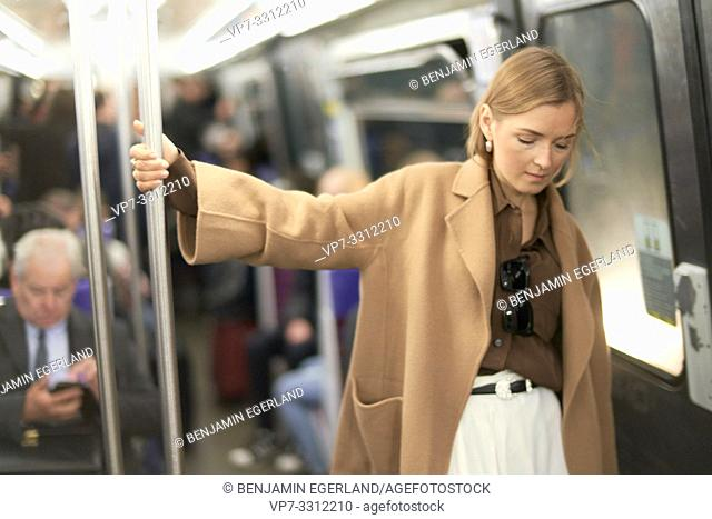 fashionable blogger woman using public transportation in city Paris, France
