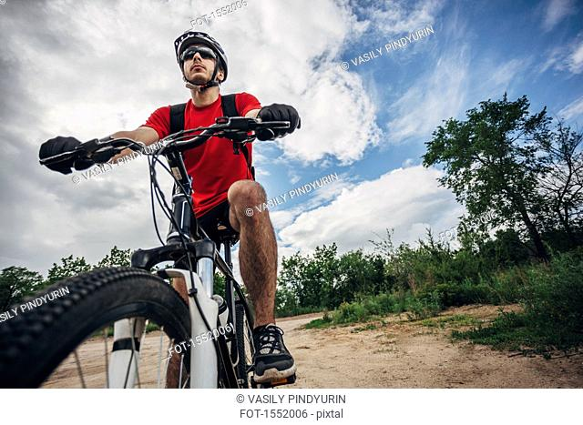 Low angle view of mountain biker riding on dirt road against sky