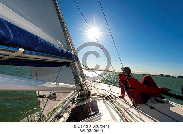 Crew member relaxing on ocean going yacht in the sun