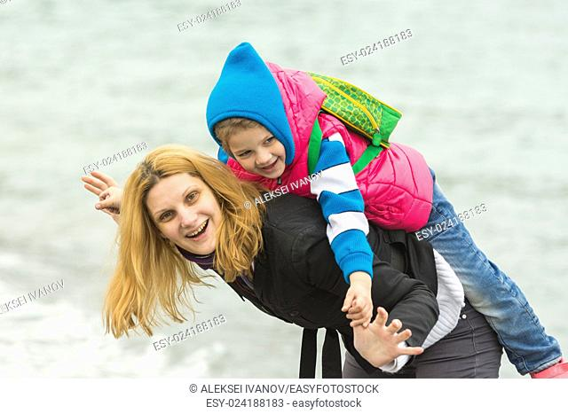 Close-up of a young girl playing with her baby on the nature near the water in cold weather