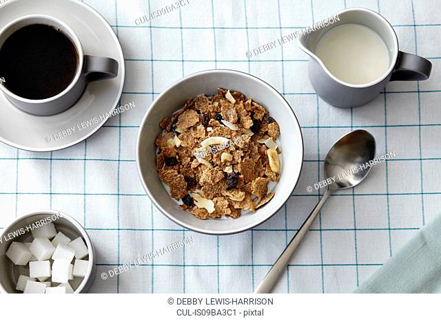 Cereal with dried fruit, coffee and milk jug, overhead view