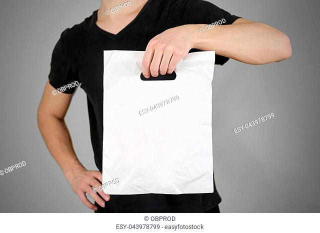 Man shows blank plastic bag mock up isolated. Empty white polyethylene package mockup. Consumer pack ready for logo design or identity presentation