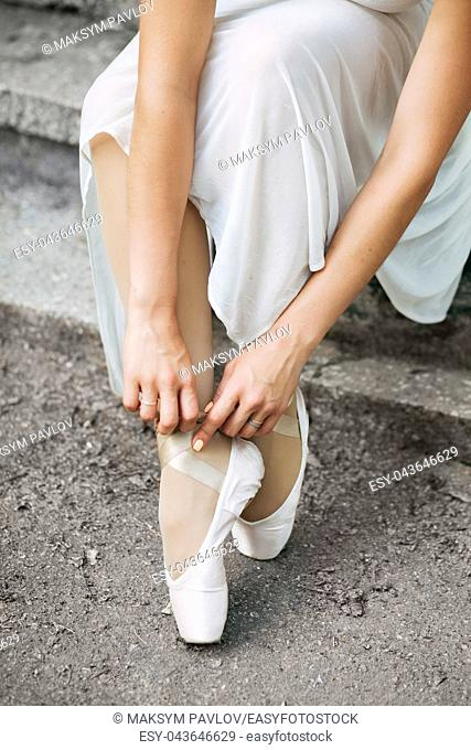 Legs of a beautiful ballerina close-up. Pointe shoes on concrete stairs