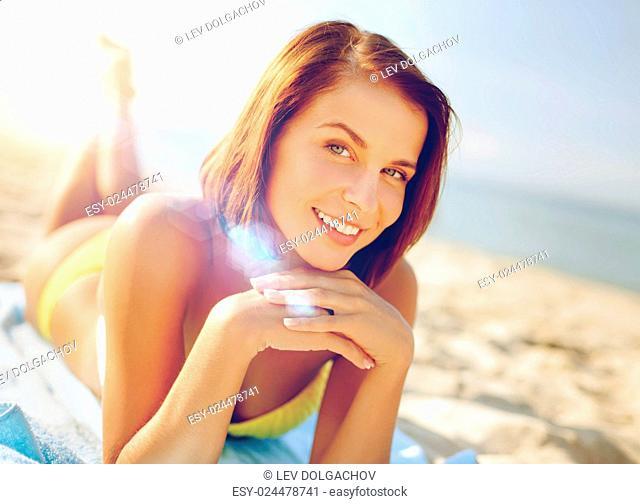 summer holidays, vacation and beach concept - girl sunbathing on the beach