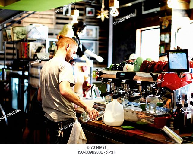 Man preparing coffee at cafe kitchen counter