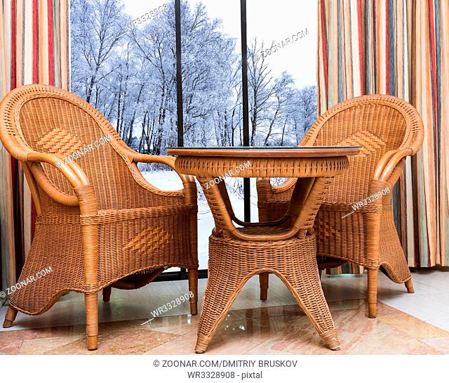 wicker furniture rattan table two chairs near the window with a winter landscape snowy trees