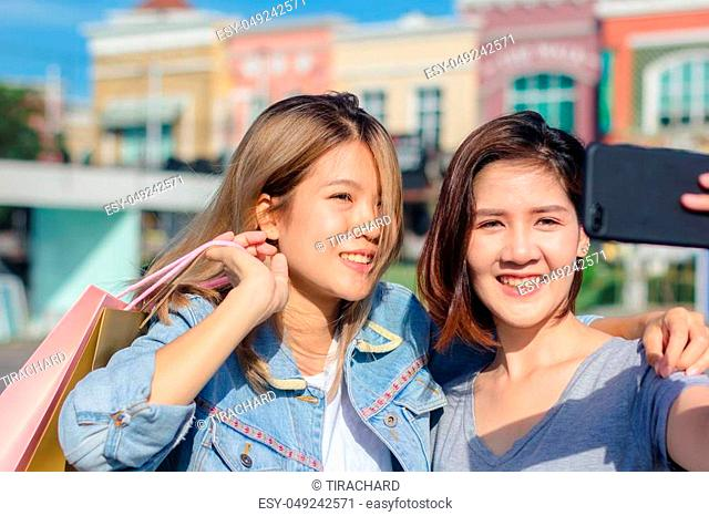 Attractive beautiful asian woman using a smartphone while shopping in the city. Happy young asian teenage at urban city while taking self portraits with her...