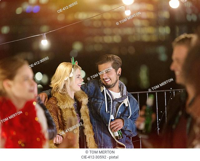 Young couple drinking and enjoying nighttime rooftop party