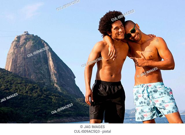 Two friends on beach with arms around each other, Rio de Janeiro, Brazil