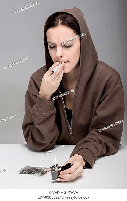 Young woman is smoking drugs, on the gray background