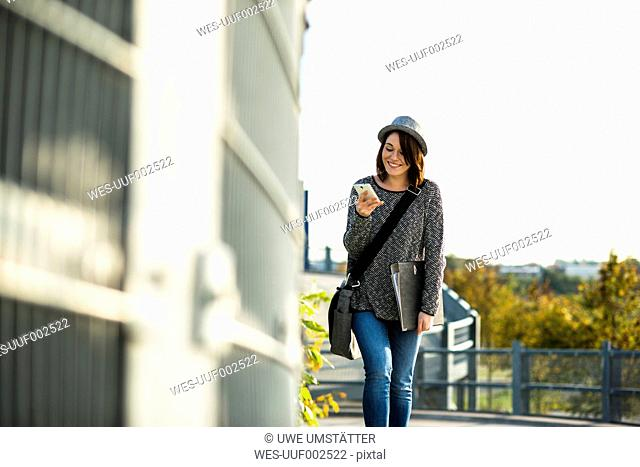 Smiling young woman with folder, bag and cell phone
