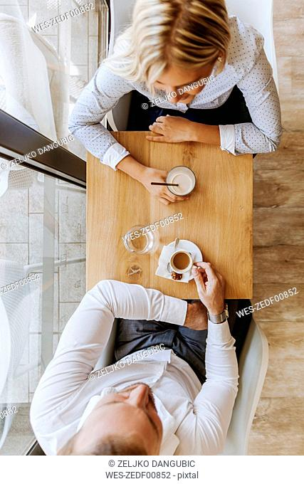 Woman and man drinking coffee in a cafe
