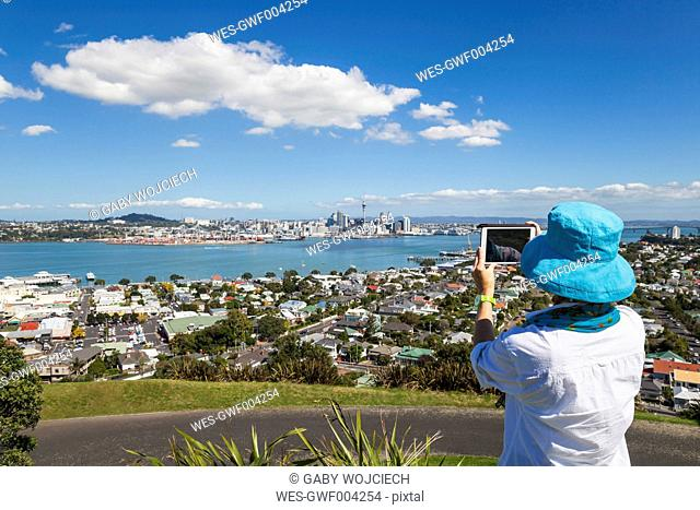 New Zealand, Auckland, New Zealand, Auckland, Tourist photographing Skyline and district Devenport in the foreground