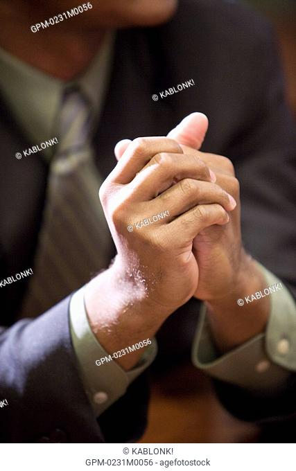 Businessman sitting at boardroom, focus on hands, close-up