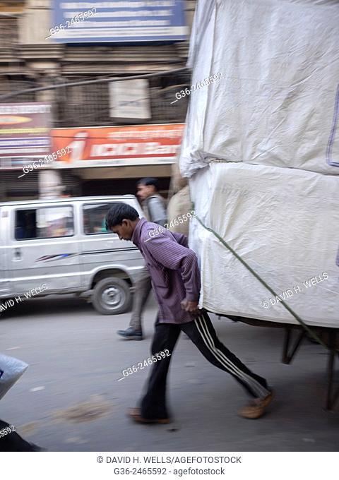 Man pulling overloaded cart, New Delhi, India