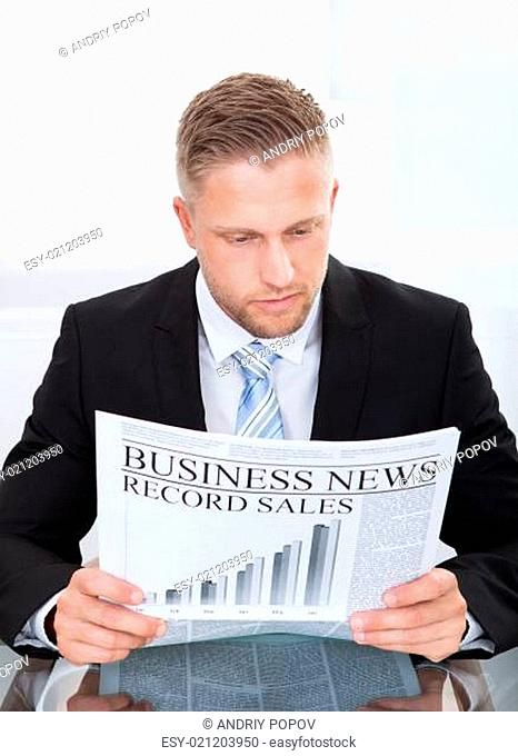 Stylish handsome businessman studying the financial newspaper
